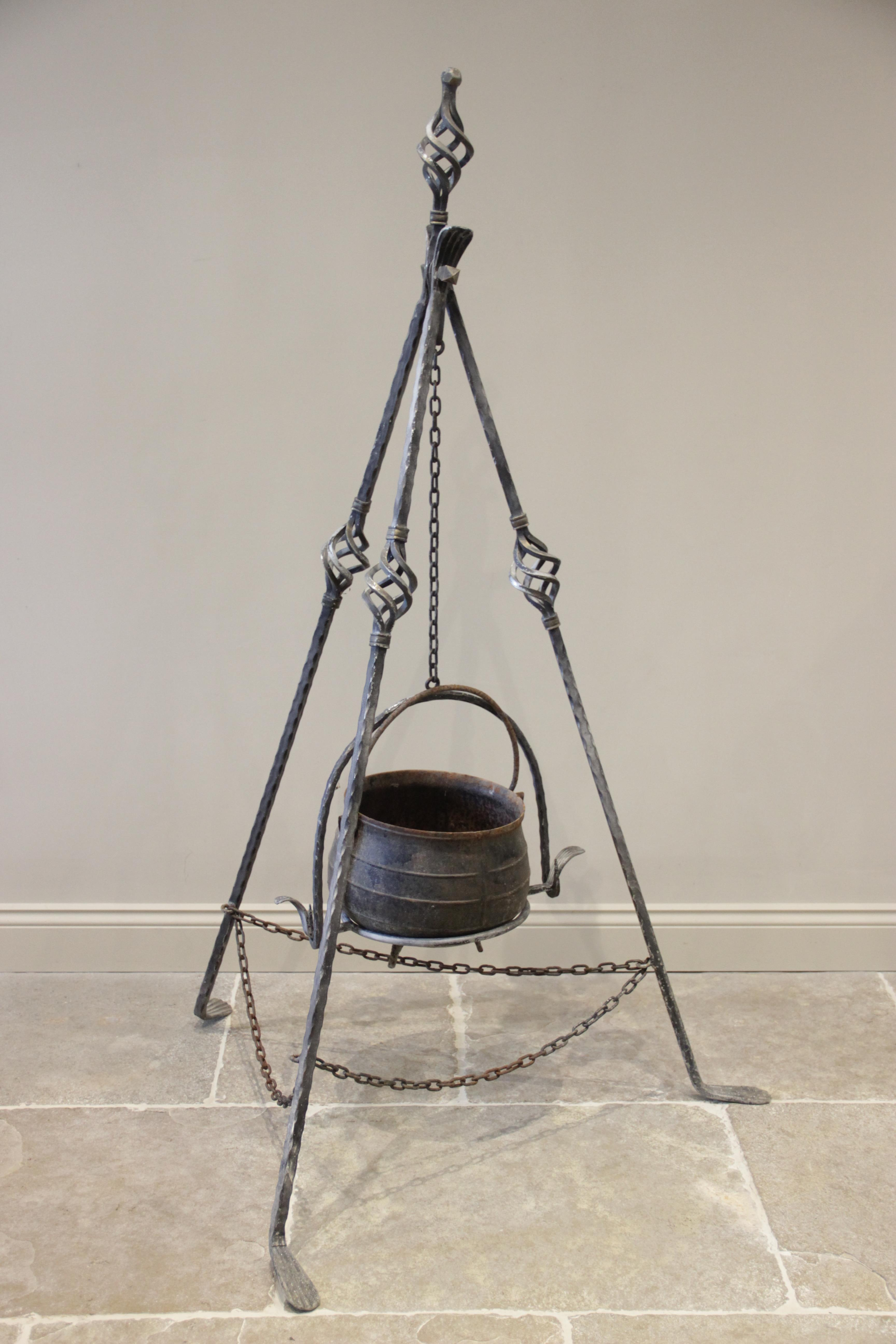A wrought iron gypsy cauldron and tripod, 20th century, the three supports with open work swelling