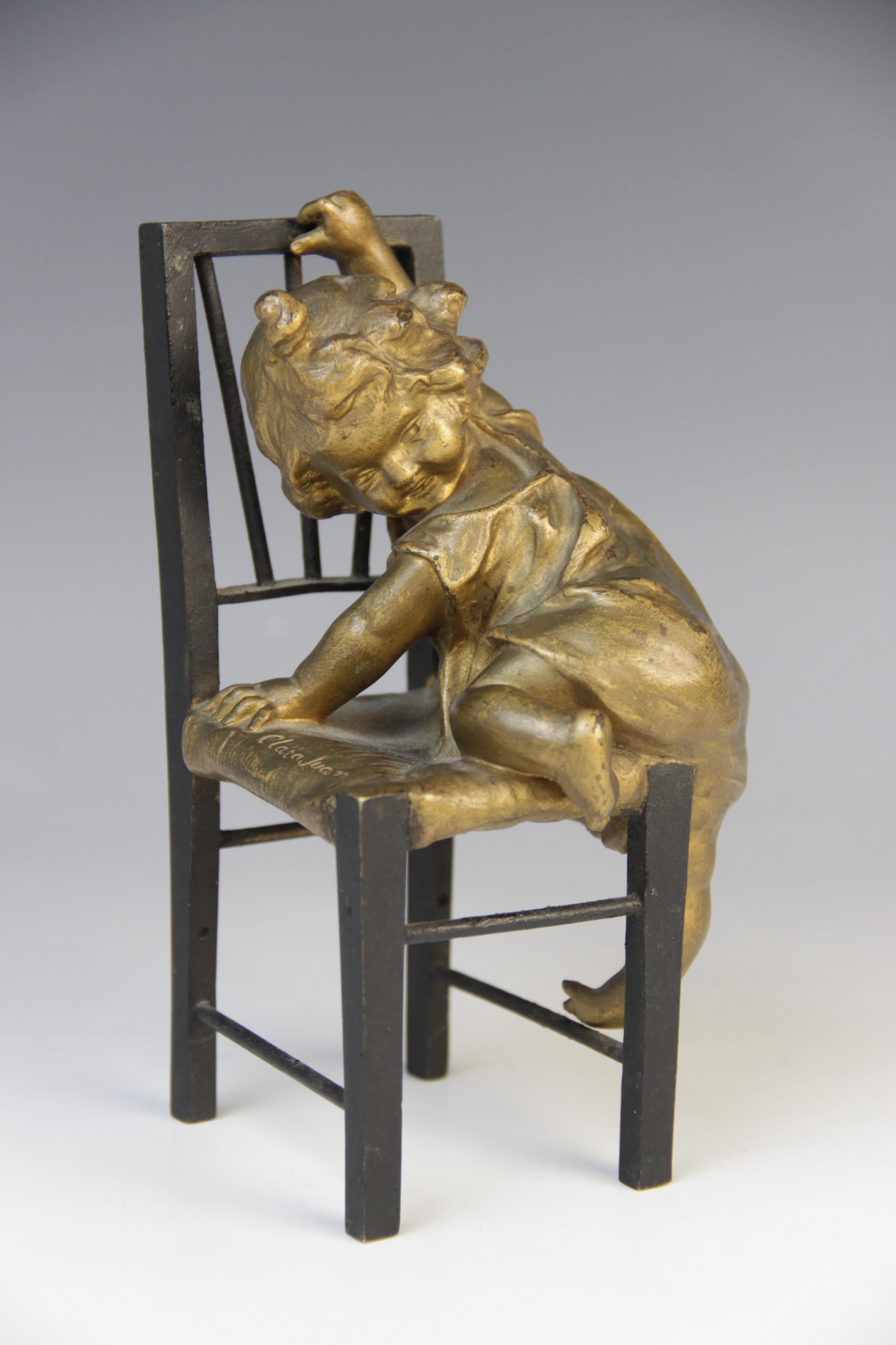 After Juan Clara (Spanish, 1857-1958), a patinated bronze and gilt figure, modelled as a child