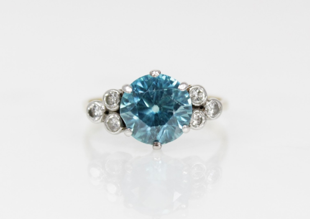 A zircon and diamond ring, the central round mixed cut blue zircon (measuring 8.65mm diameter),