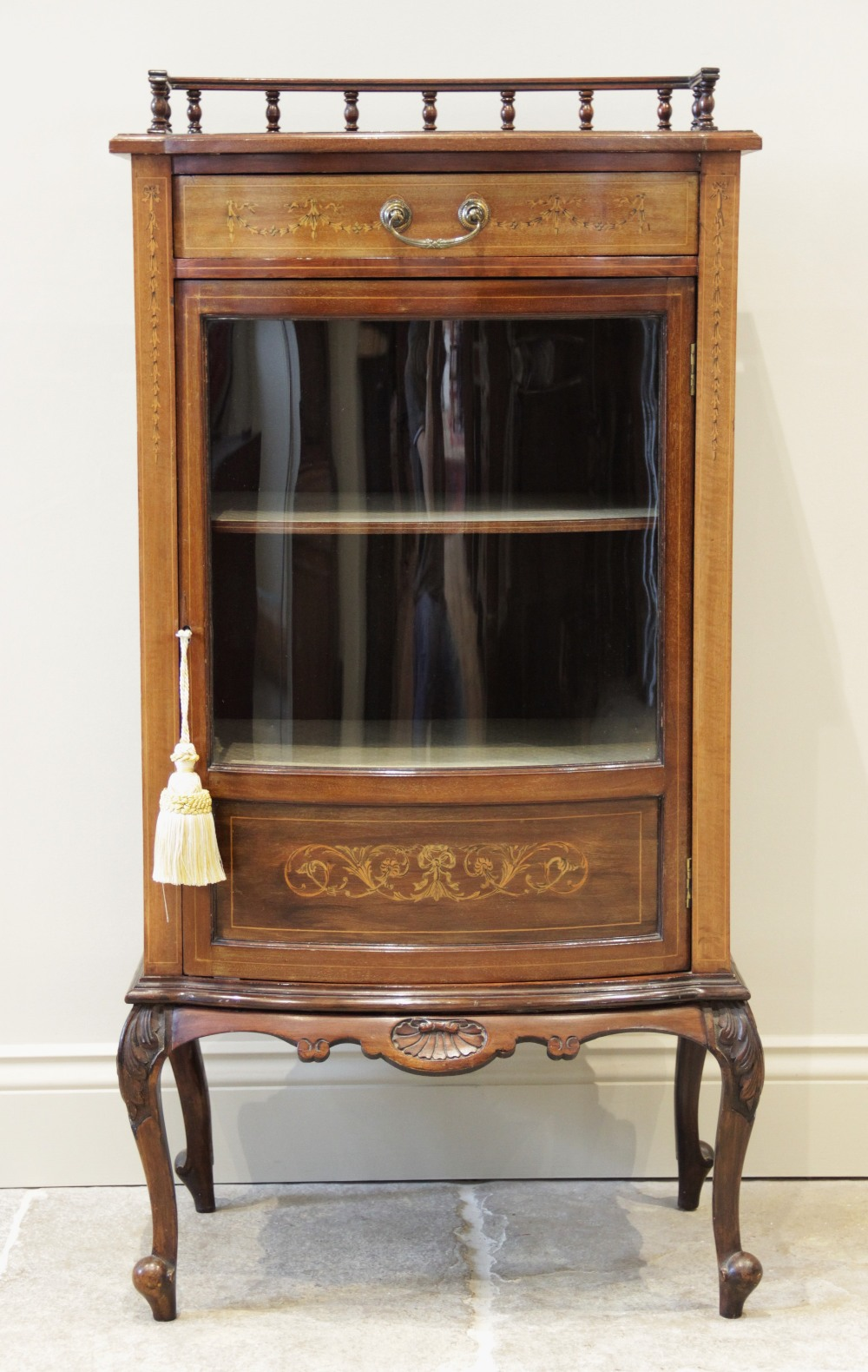 An Edwardian mahogany bowfront display cabinet, the shaped top with a rear spindle gallery, above