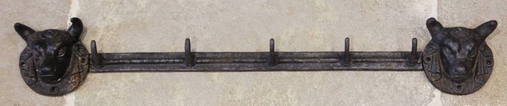 A cast iron wall mounted coat or hat rack, the five hook rail applied to the wall by a pair of