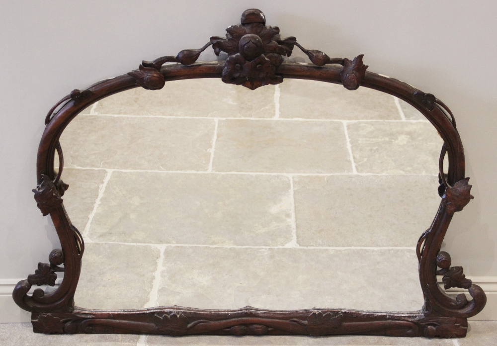 A Victorian stained and carved hardwood over mantel mirror, the carved leafy crest extending to