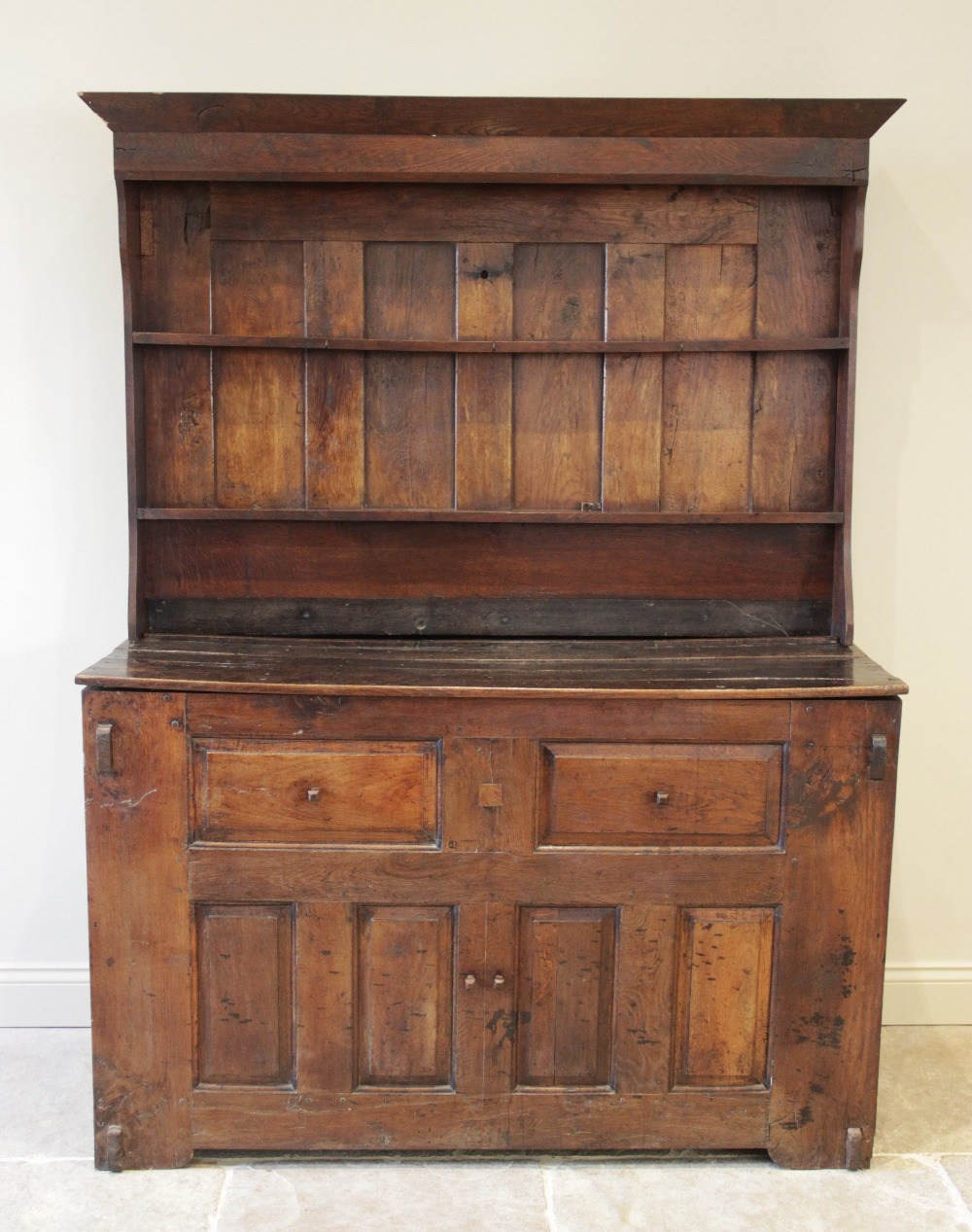 An 18th century and later oak Welsh dresser, the associated rack with a moulded cornice over two