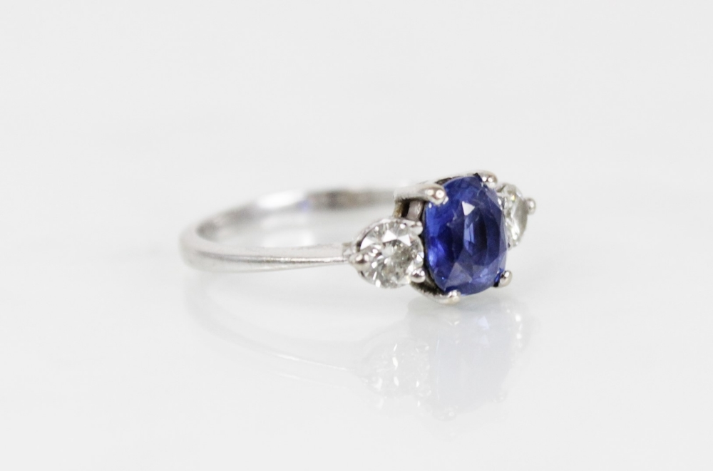 A sapphire and diamond three-stone ring, the (untested) central mixed, cushion cut sapphire ( - Image 5 of 8