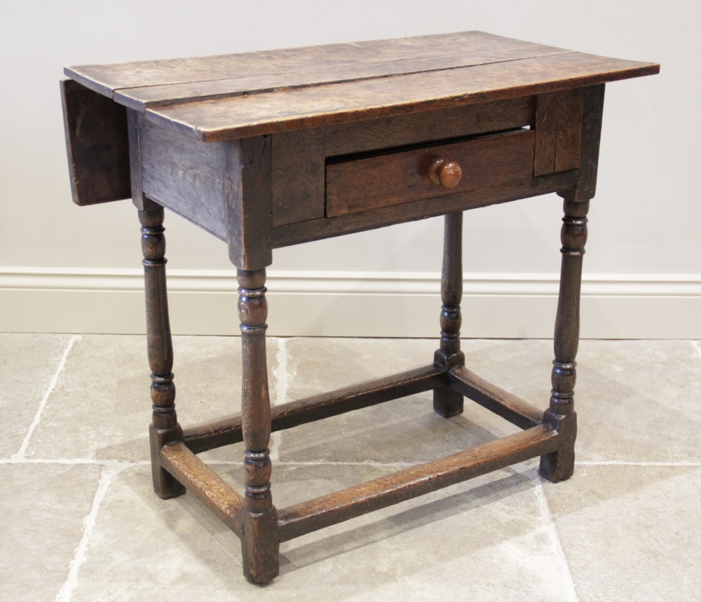 An early 18th century oak single drop leaf side table, the plank top above a single frieze drawer,