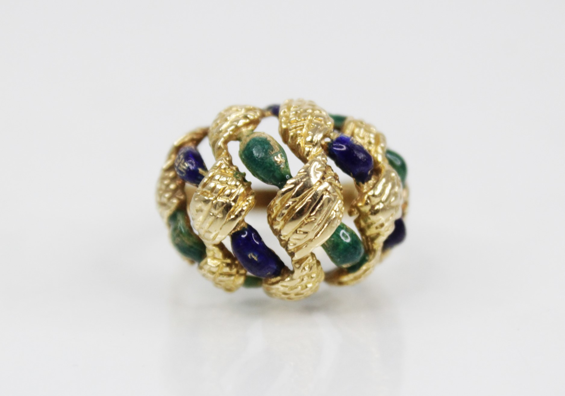An 18ct gold enamelled 'bombe' ring, the openwork woven design head with textured engraving and blue