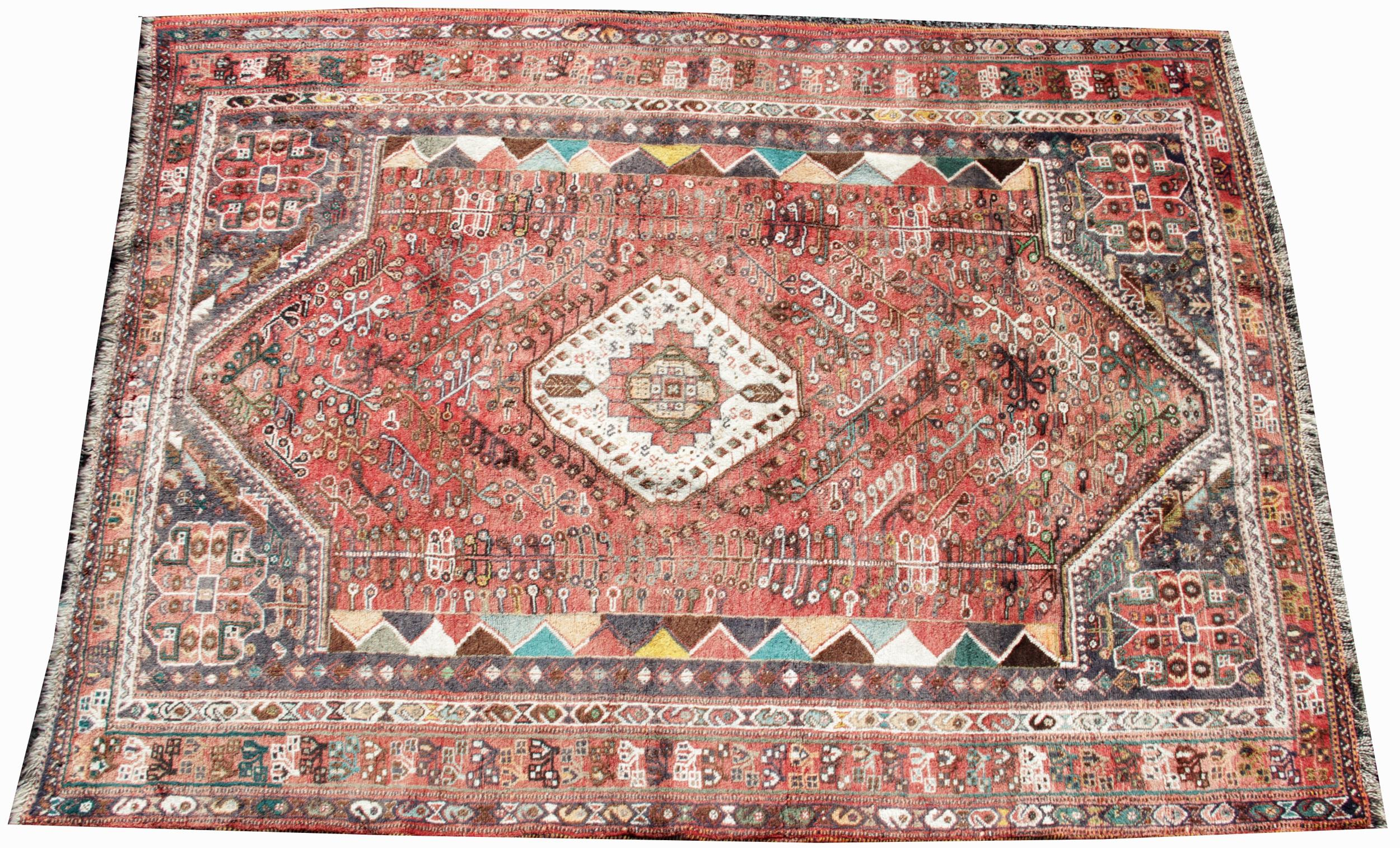 A Turkish wool rug, the central white lozenge shaped medallion upon a red ground, enclosed by red