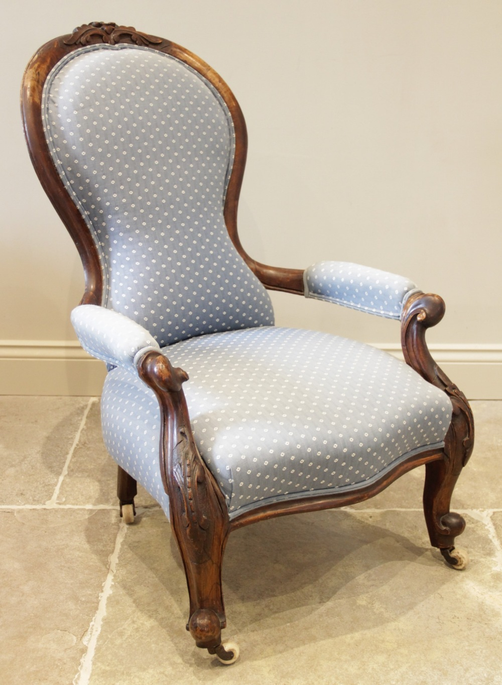 A Victorian walnut spoon back open armchair, in blue fabric, with a leaf carved crest above the