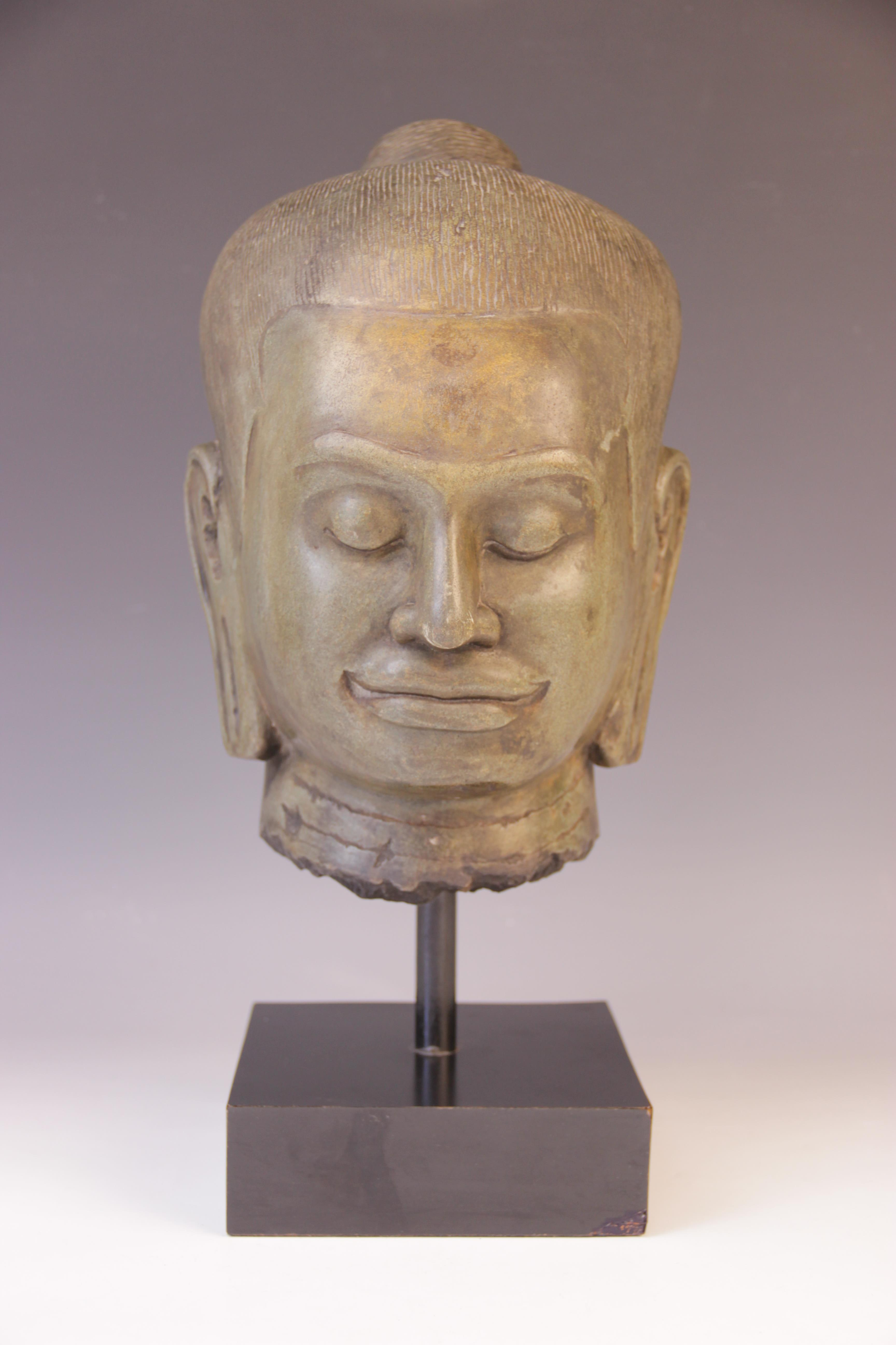 A Verdigris bronzed head of Guanyin, 20th century, modelled upon a stand, 41cm high