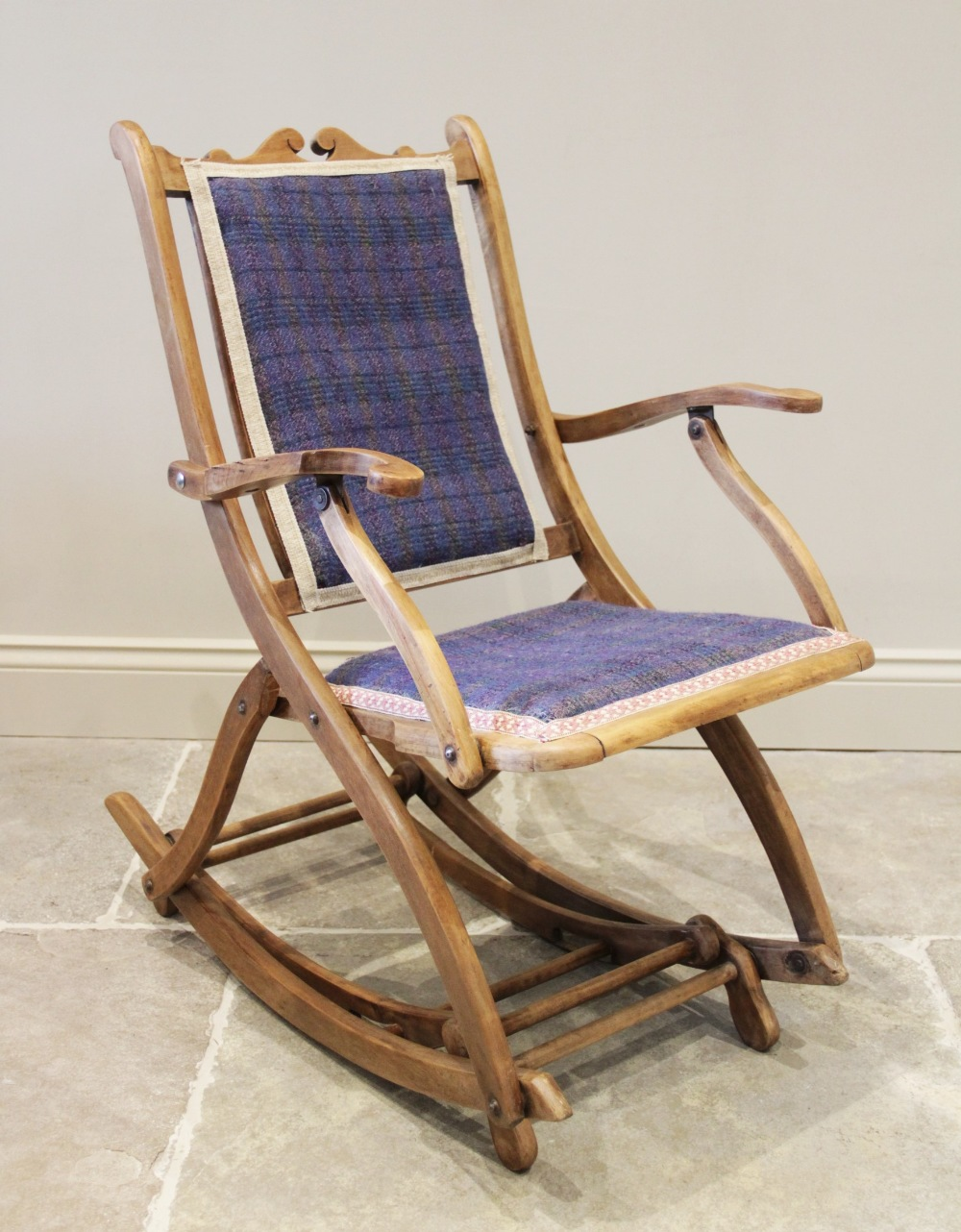 A late 19th century adjustable beech wood rocking chair, probably French, with a padded back rest