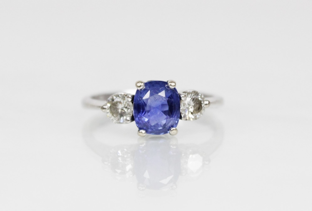 A sapphire and diamond three-stone ring, the (untested) central mixed, cushion cut sapphire ( - Image 3 of 8