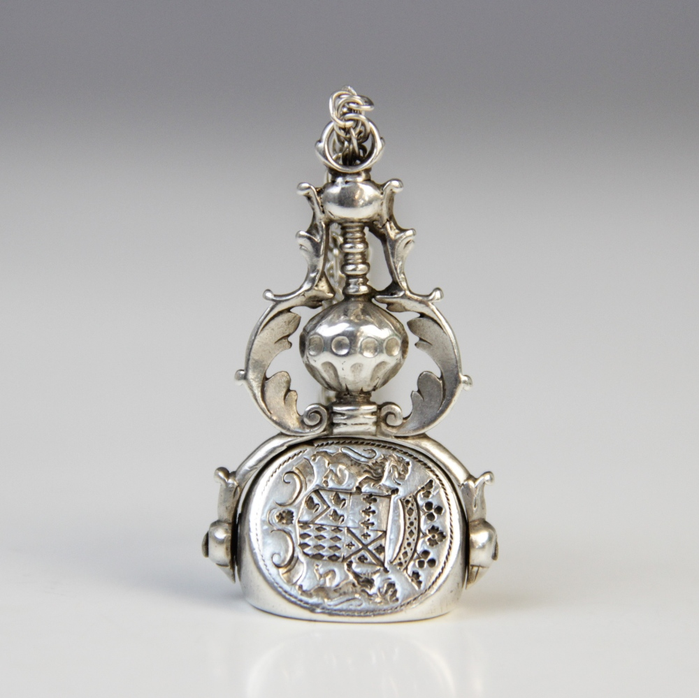 A 19th century silver coloured three-sided swivel fob pendant, each oval face with an engraved