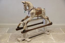 A late Victorian dapple grey rocking horse, applied with leather saddle and reins, with inset