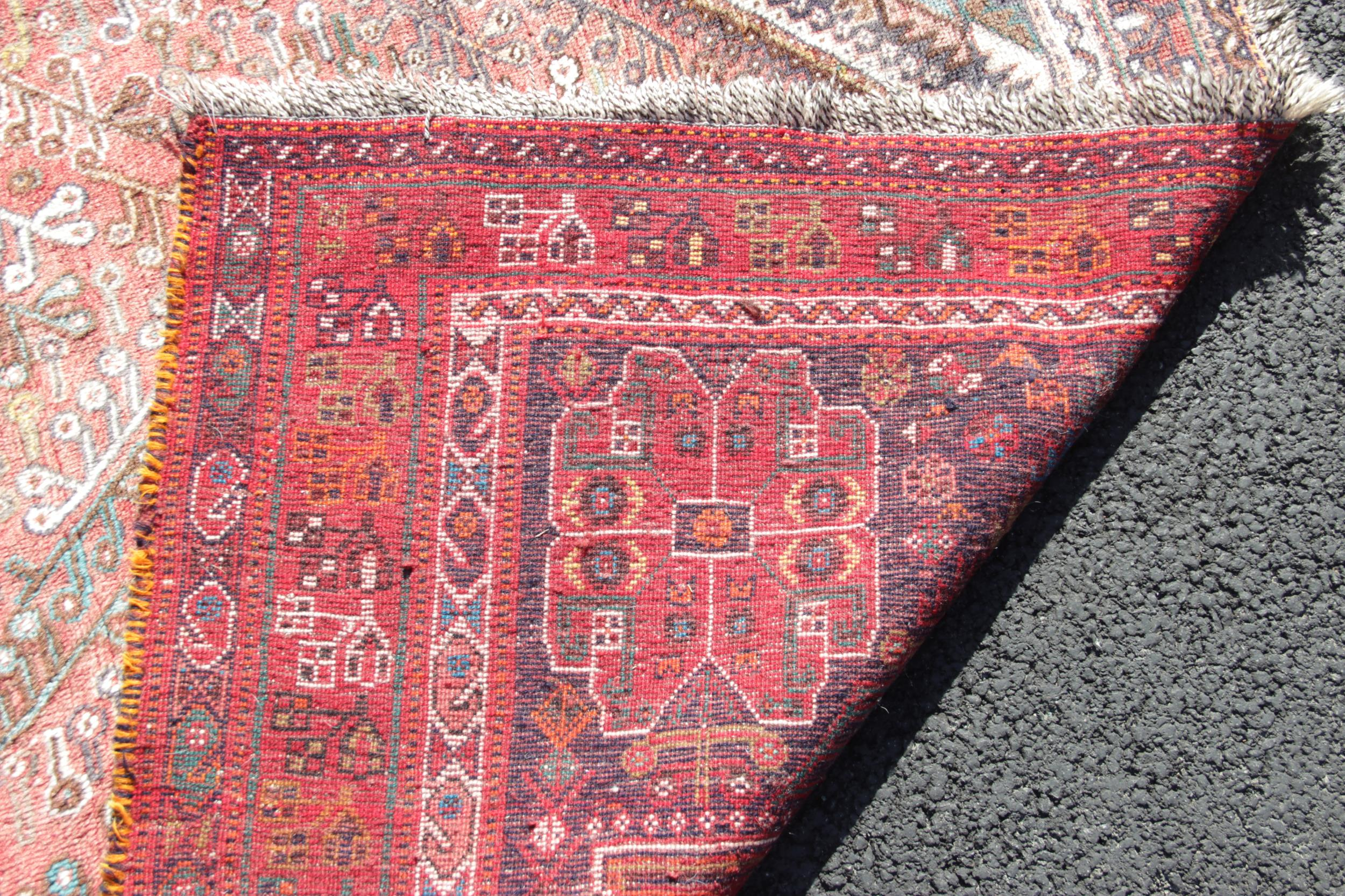 A Turkish wool rug, the central white lozenge shaped medallion upon a red ground, enclosed by red - Image 2 of 2