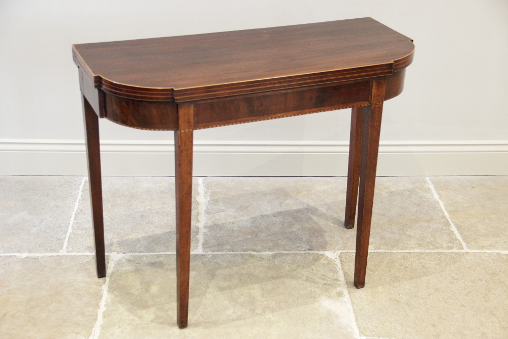 A George III mahogany folding tea table, the shaped top with inlaid satinwood stringing to the edge,