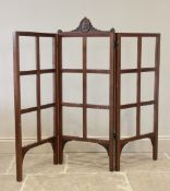 A 19th century mahogany three panel folding screen, the central panel surmounted with a carved