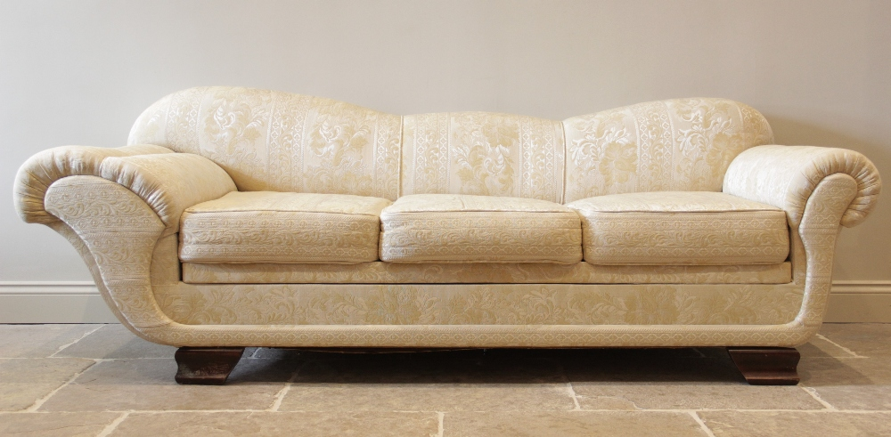 An Empire style padded scroll end day bed, in cream coloured fabric, the scalloped padded back and