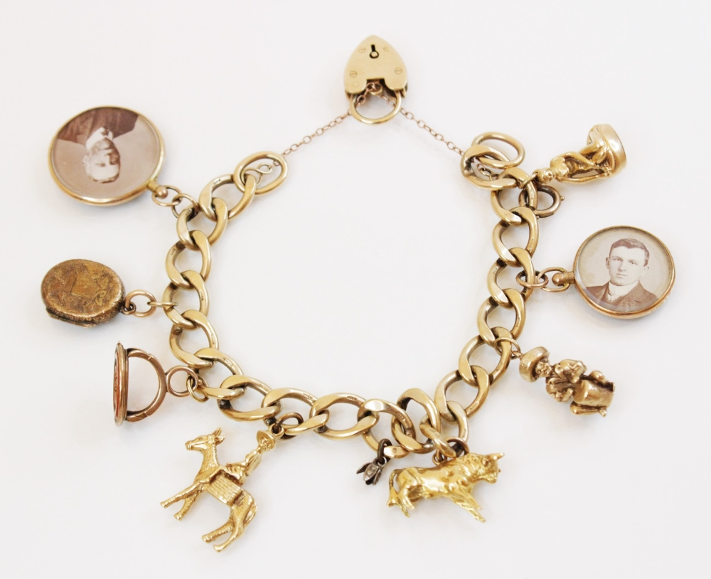 A 9ct gold curb-link charm bracelet with a heart-shaped padlock fastener, 18cm long, suspending an