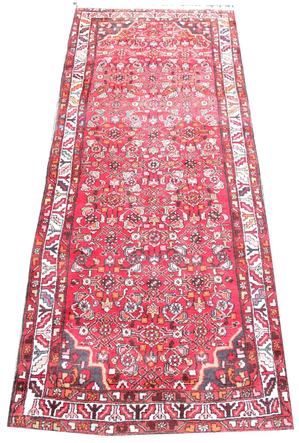 A hand knotted Persian wool runner, the central panel with a trailing geometric pattern upon a