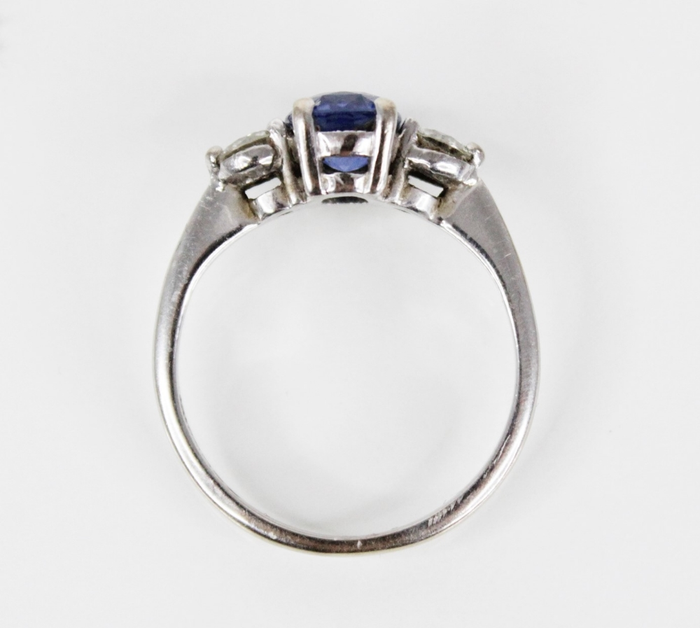 A sapphire and diamond three-stone ring, the (untested) central mixed, cushion cut sapphire ( - Image 7 of 8