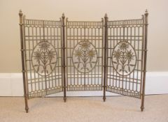 A brass floral three panel fire screen, 20th century, each panel of trellis form with central cast