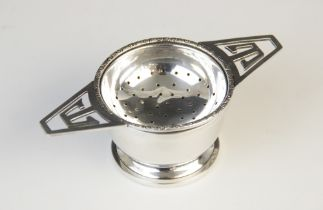 A George IV silver tea strainer and stand by G W Lewis & Co, Birmingham 1941, the circular bowl with