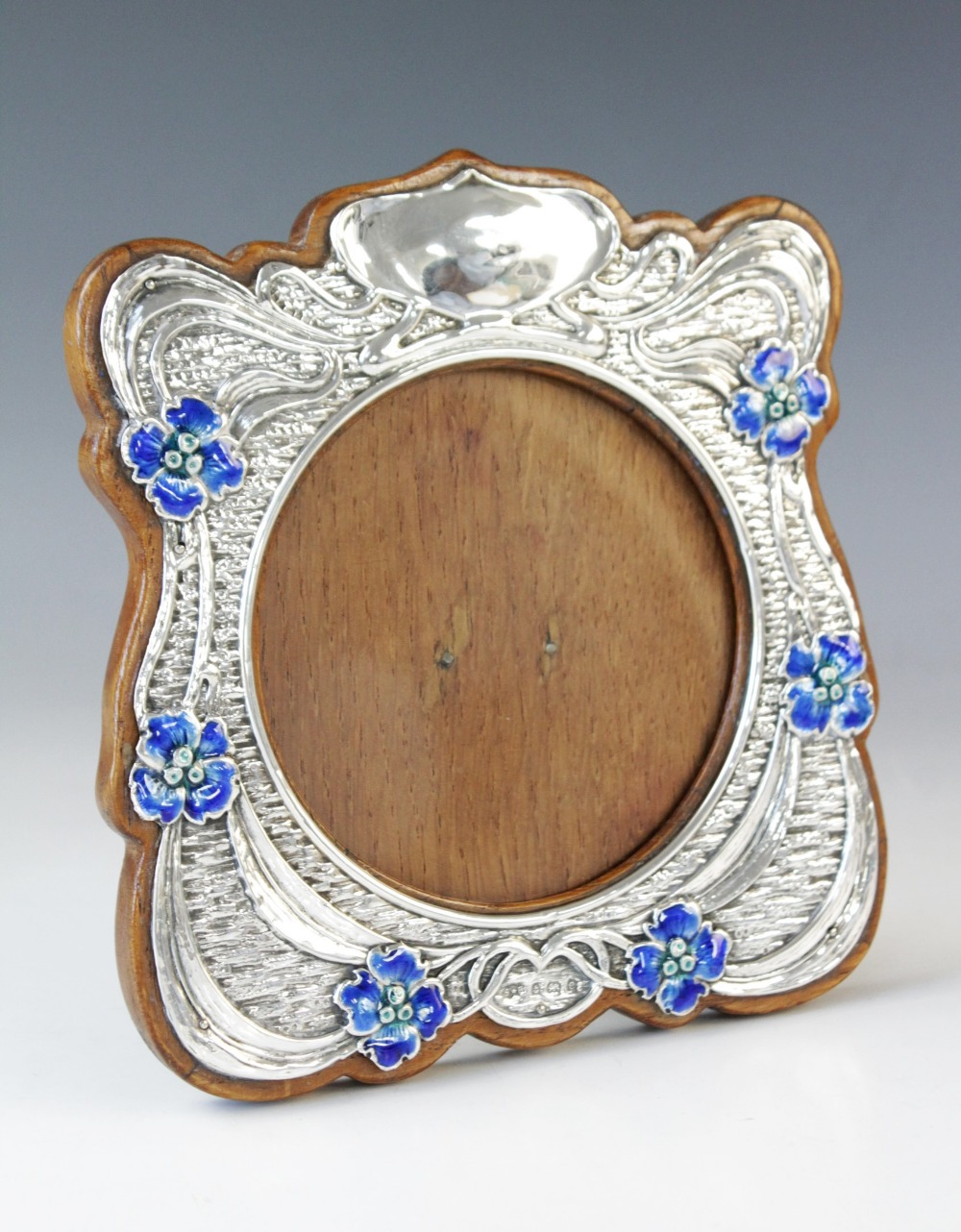 An Art Nouveau silver and enamel photograph frame, Synyer & Beddoes, Birmingham 1904, of shaped