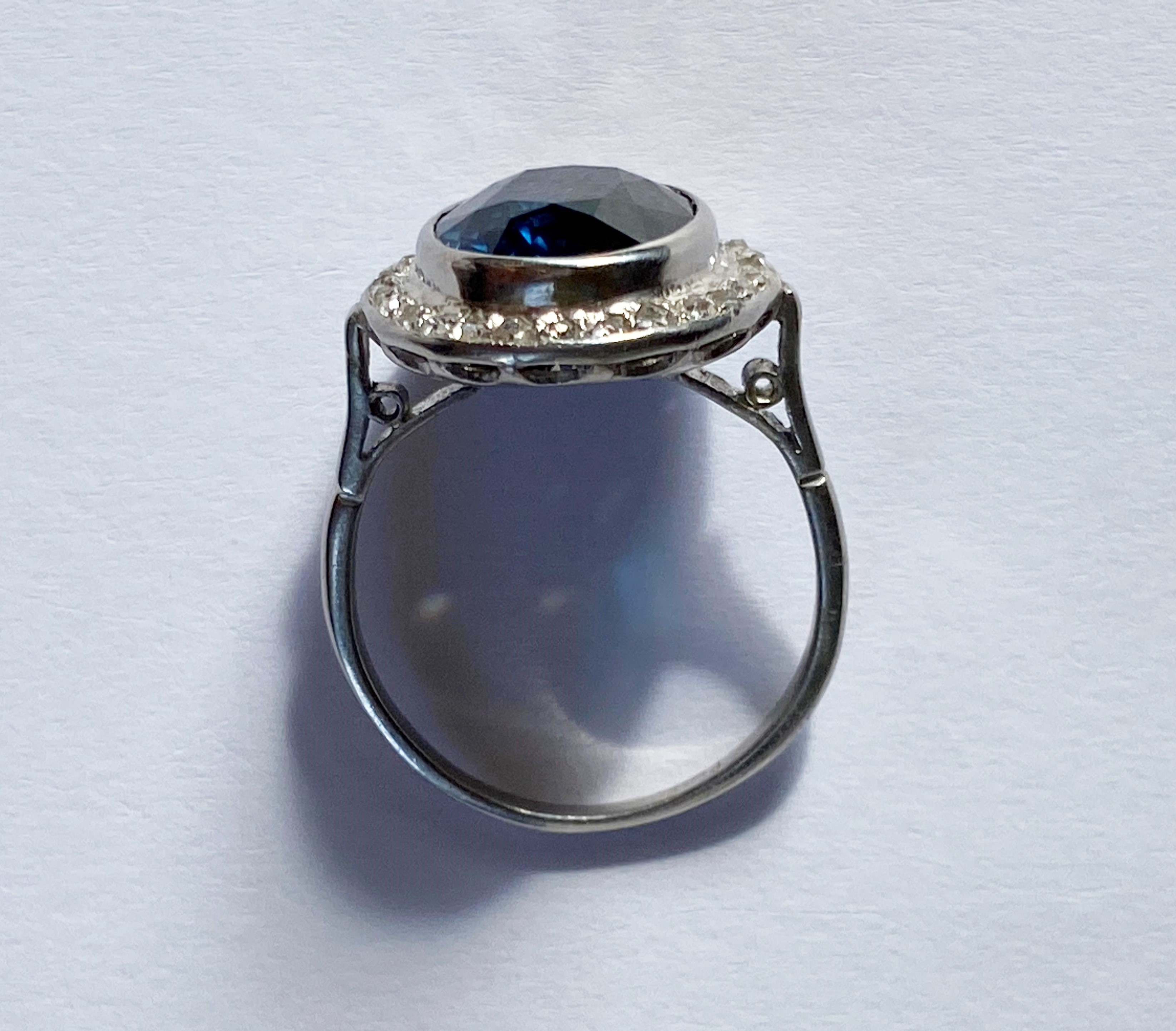 A sapphire and diamond cluster ring, the central oval mixed cut blue sapphire (measuring 12.20mm x - Image 6 of 7