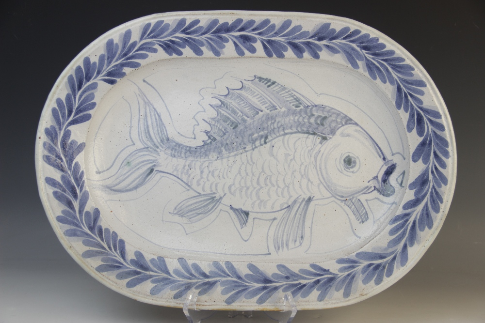 A Cooper Pottery studio pottery fish plate, of oval form, applied with a central blue fish on a