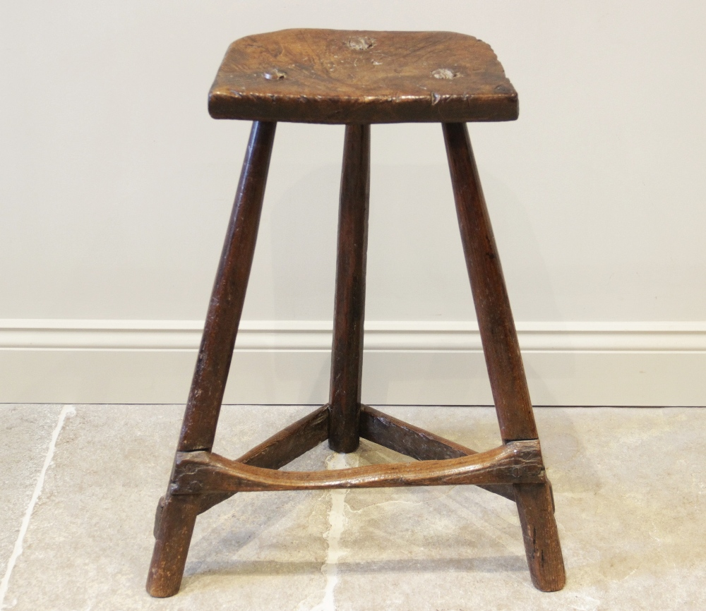 An early 19th century ash and elm primitive cutlers stool, the rough cut slab top raised upon