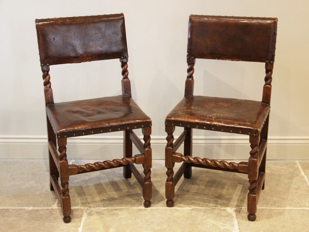 A pair of Charles II style oak chairs, 19th century and later, each chair with a studded leather