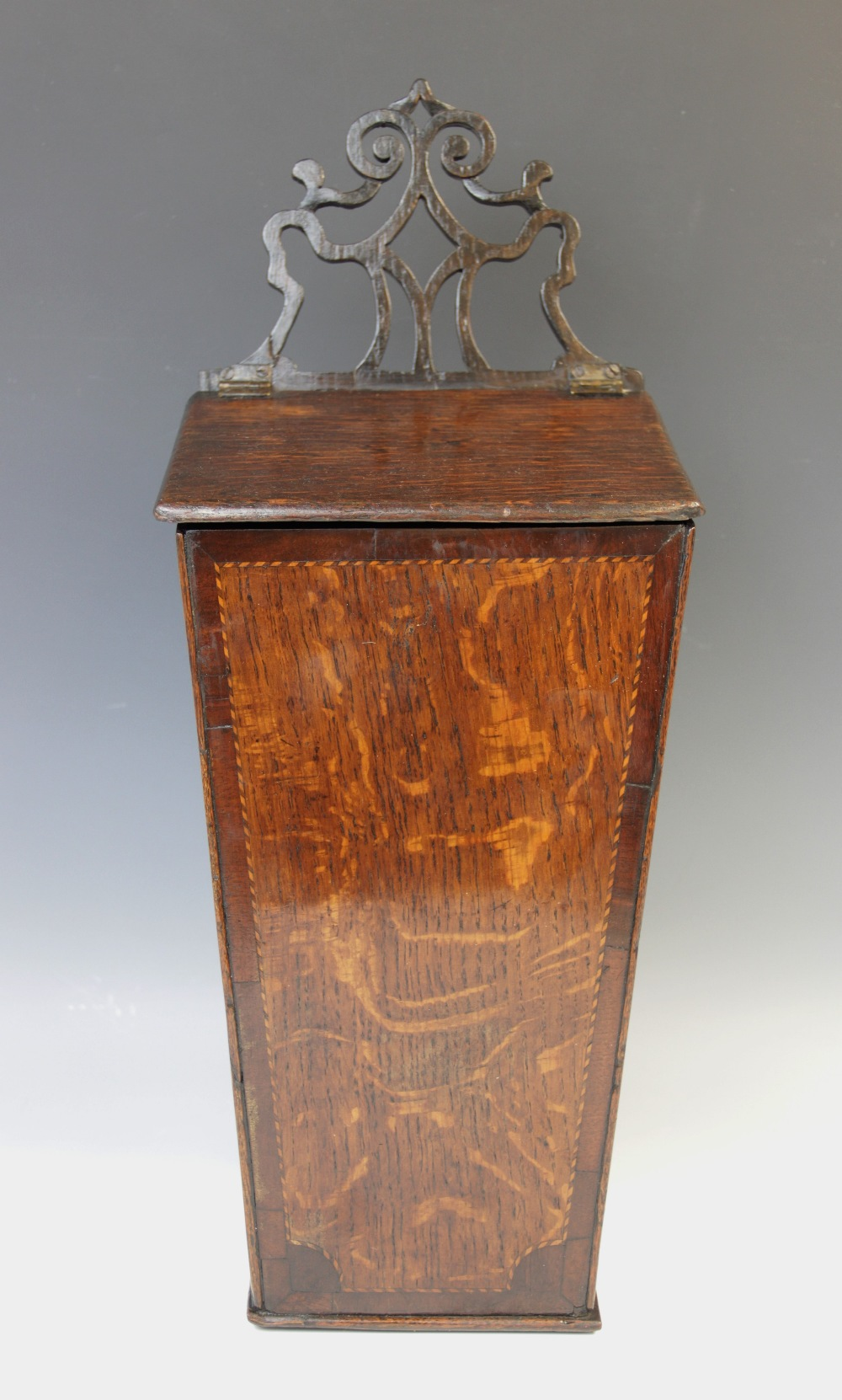 A George III oak and mahogany cross banded candle box, of typical tapering form, with associated
