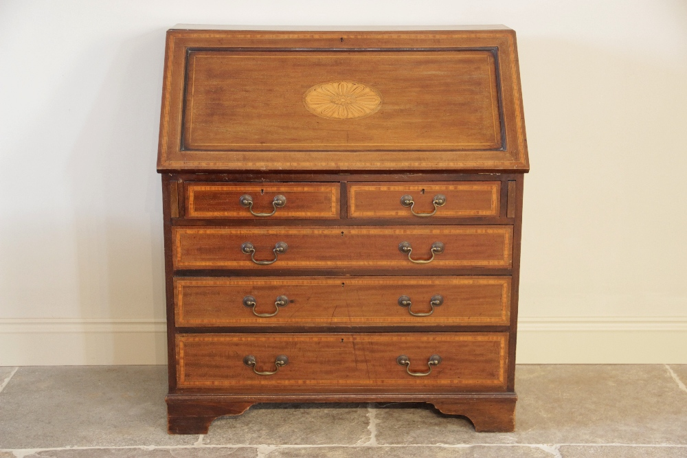 An Edwardian Sheraton revival mahogany and satinwood crossbanded bureau, the fall front centred with