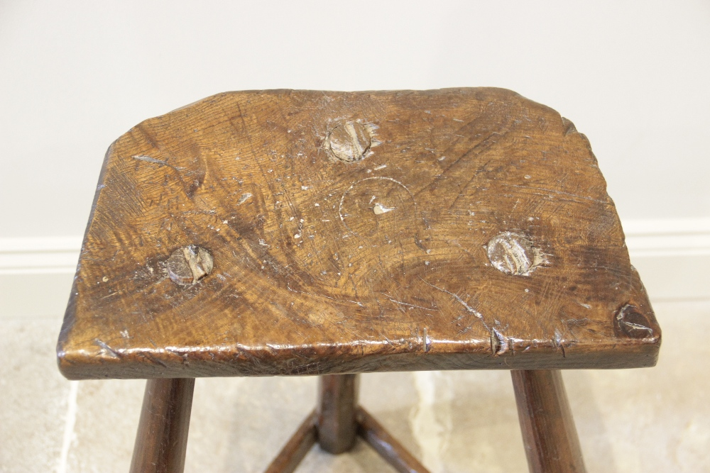 An early 19th century ash and elm primitive cutlers stool, the rough cut slab top raised upon - Image 3 of 5