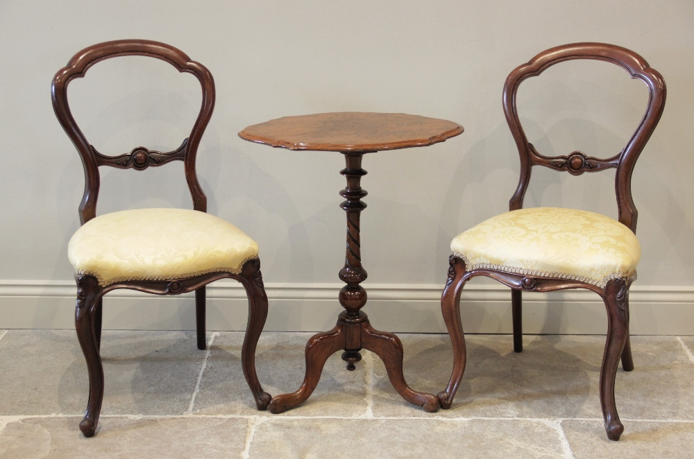 A mid 19th century walnut pedestal occasional table, the shaped and figured top raised upon a turned