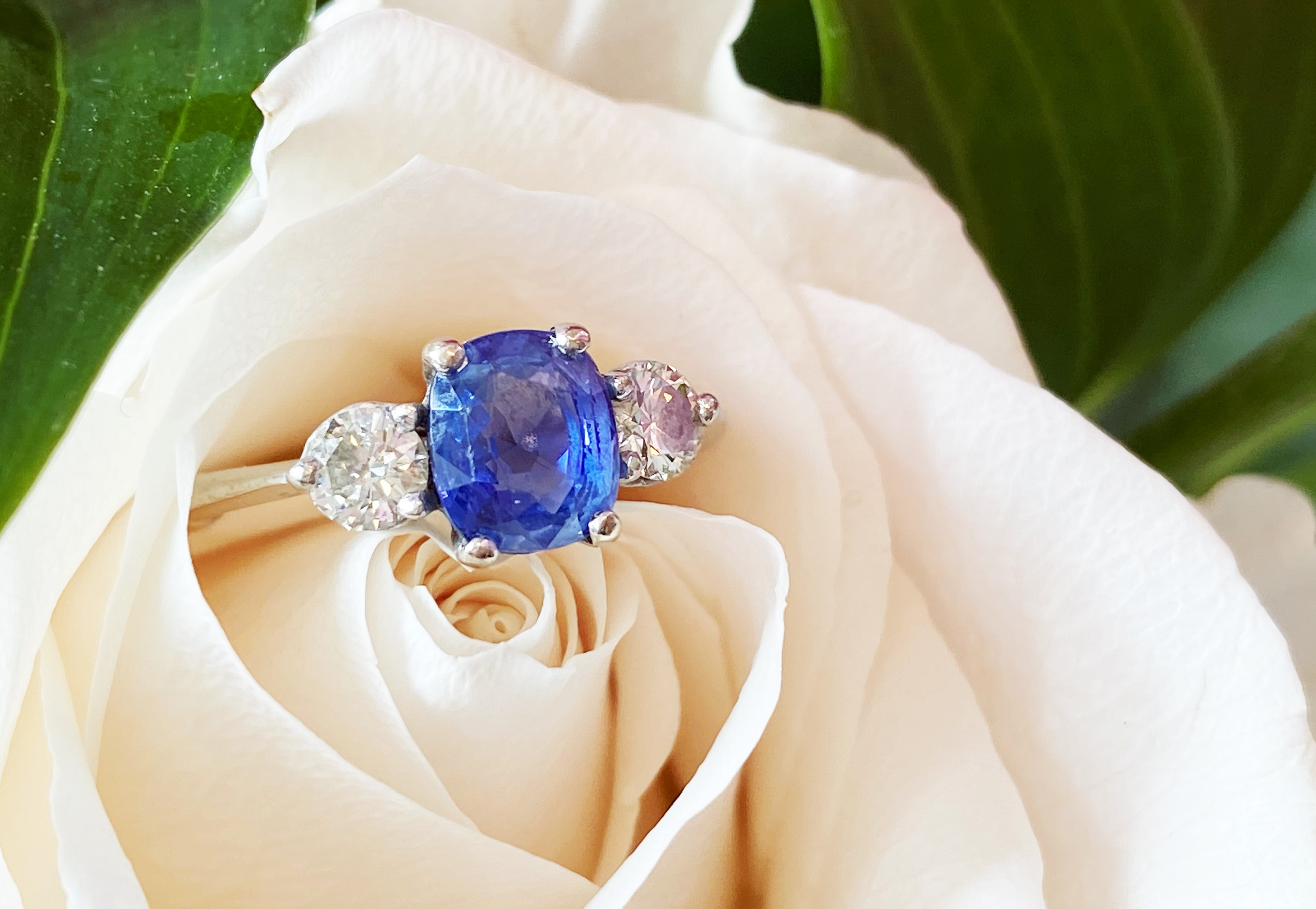 A sapphire and diamond three-stone ring, the (untested) central mixed, cushion cut sapphire (