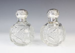 A pair of late Victorian silver mounted cut glass scent bottles by John Grinsell & Sons,