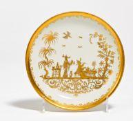 UNTERSCHALE MIT GOLDCHINOISERIEN. In der Art von Meissen. Porzellan gold dekoriert. ø 12cm.