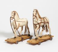 2 SPIELZEUGPFERDE AUF ROLLEN. Holz geschnitzt, farbig gefasst, Lederbänder, u.a. H.38, L.39/ H.41,