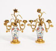 PAAR ZWEIFLAMMIGE LEUCHTER MIT CHINOISEM DEKOR. Porzellan farbig dekoriert, Metall vergoldet. H.30/