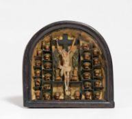 Kleiner Schaukasten mit Kruzifix flankiert von Totenschädeln