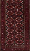 A Baluchi rug, IranWool and cotton of geometric pattern in bordeaux, blue and beige shades<b