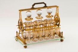 A Baccarat tantalusGilt bronze stand with glass base and bottle lock Three bottles and 12 gilt d