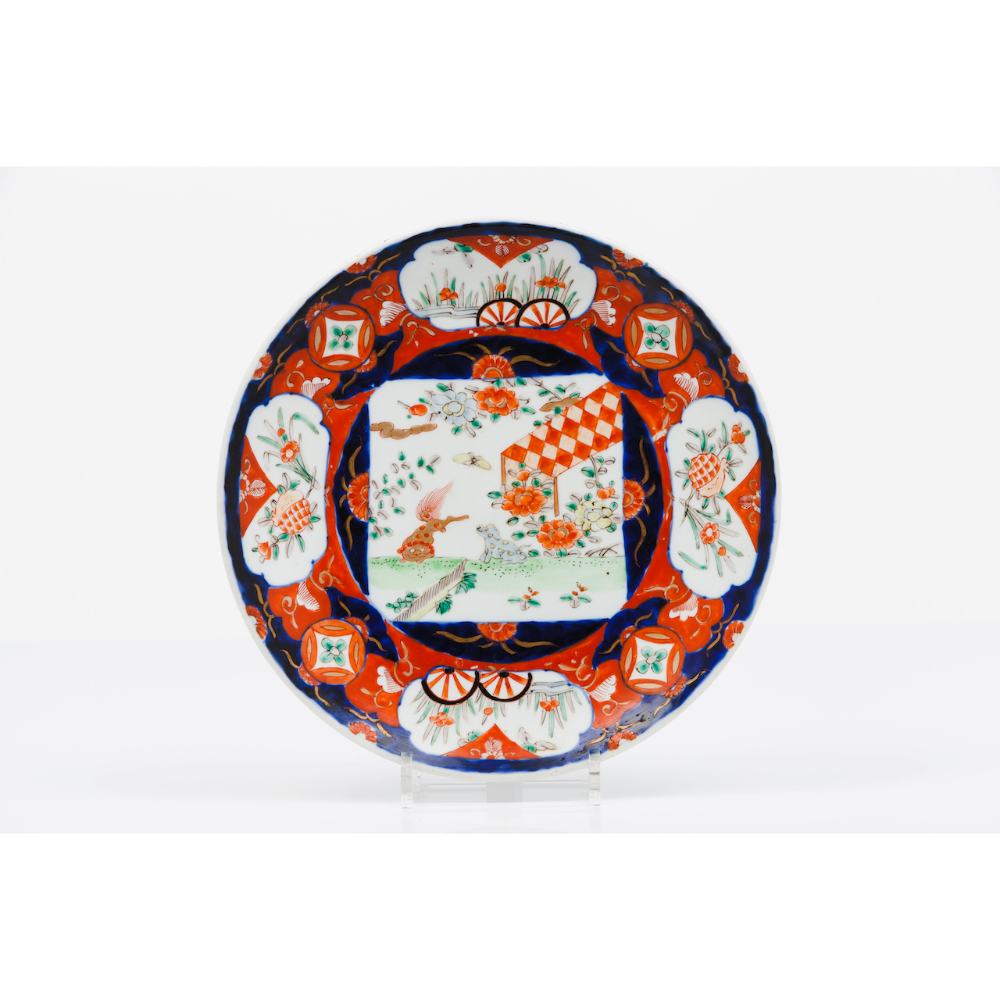 A plateJapanese porcelain Imari decoration of central landscape with animals and foliage motifs 19th