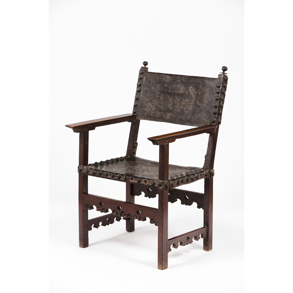 An armchairChestnut and other timbers Embossed leather seat and back with decorative brass tacks