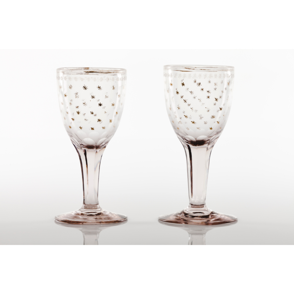 """A pair of footed drinking glasses""""La Granja"""" factory moulded glass Faceted shaft Gilt stars"""