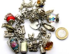 Silver charm bracelet with 25 charms, 130g. P&P Group 1 (£14+VAT for the first lot and £1+VAT for