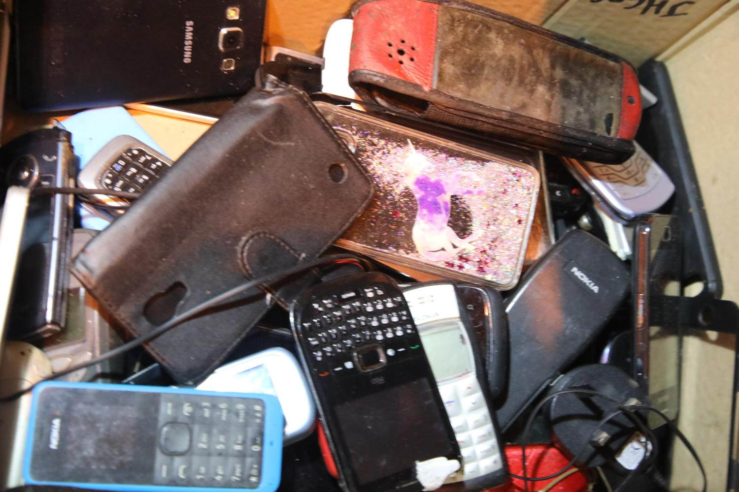 Tray of mixed mobile phones including iPhones and Samsung Blackberry Nokia. Not available for in-