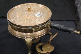 Eastern copper relief decorated warming pan, sitting on stand with burner. P&P Group 3 (£25+VAT