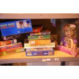 Shelf of mixed children's toys and games including Disney Rapunzel styling head. Not available for